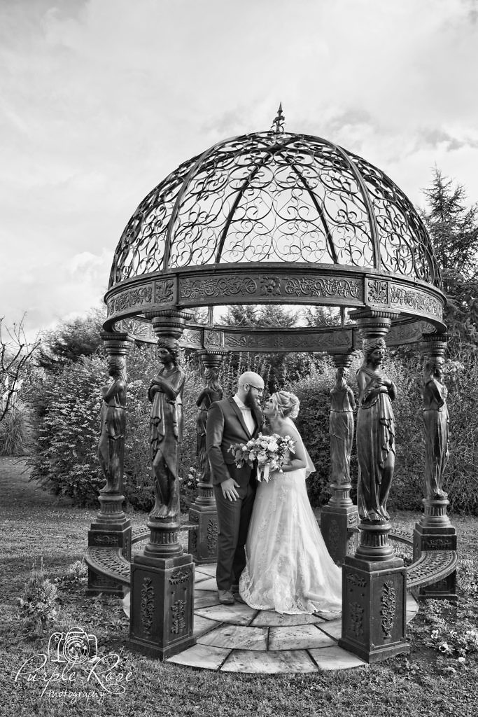 Bride and groom enjoying a quiet moment together in the garden of their wedding venue