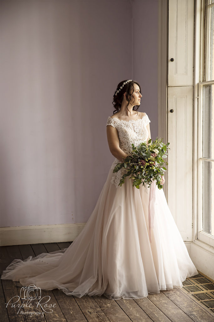 Bride standing by a tall window
