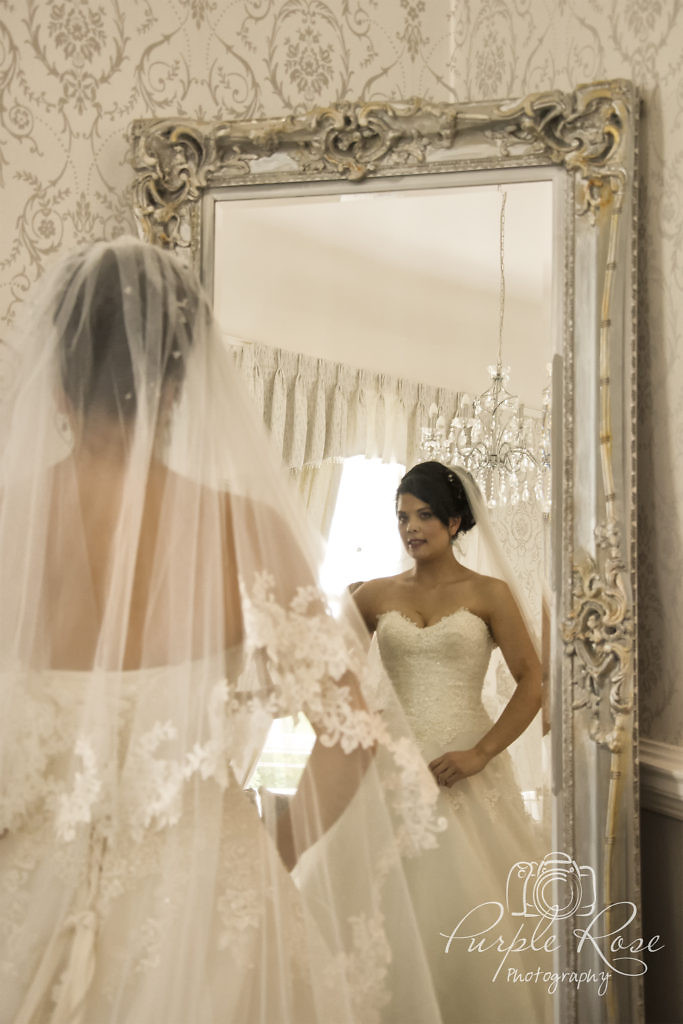 Bride checking her reflection in the mirror.