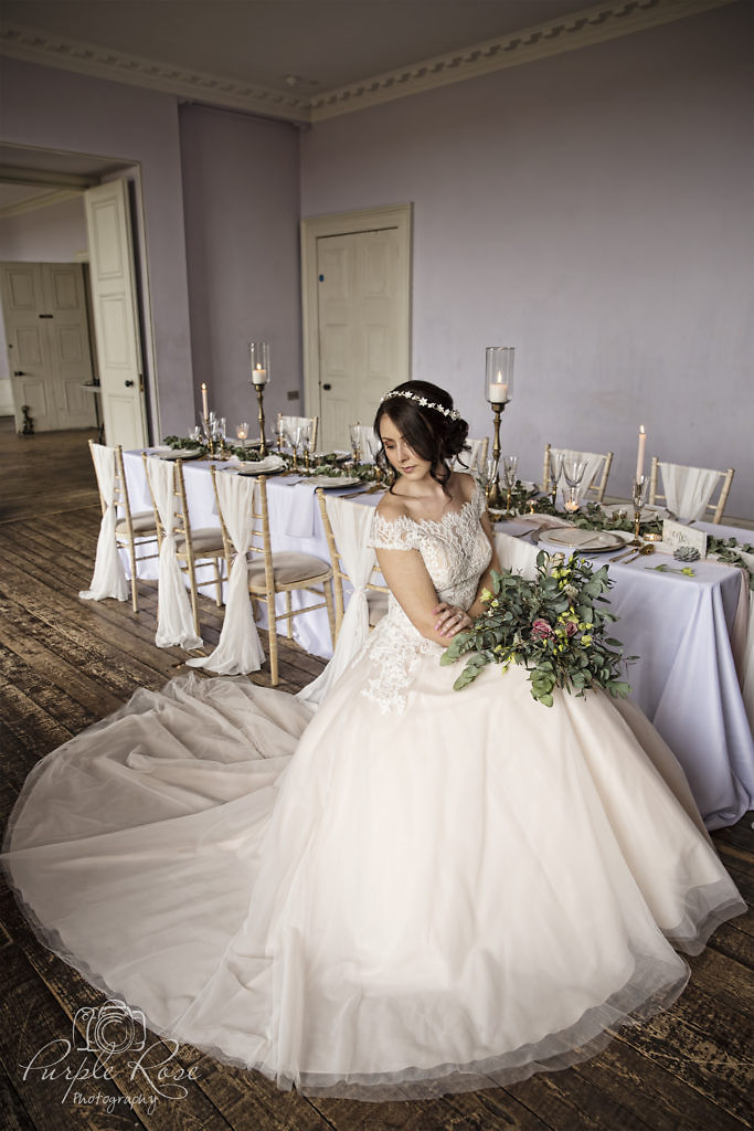 Bride sat on chair with her dress flowing around her