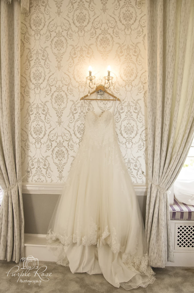 Brides wedding dress hanging on the wall