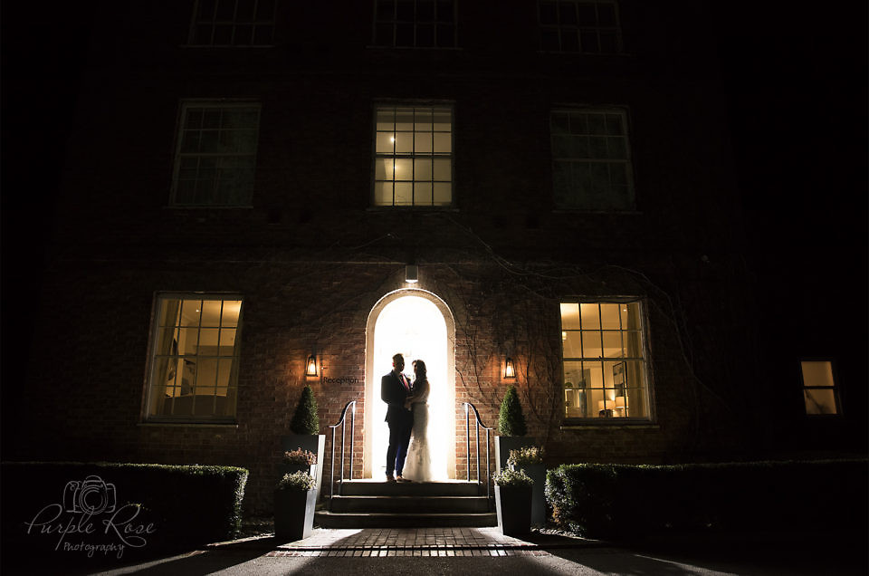 Night time photo of bride and groom in front of their venue