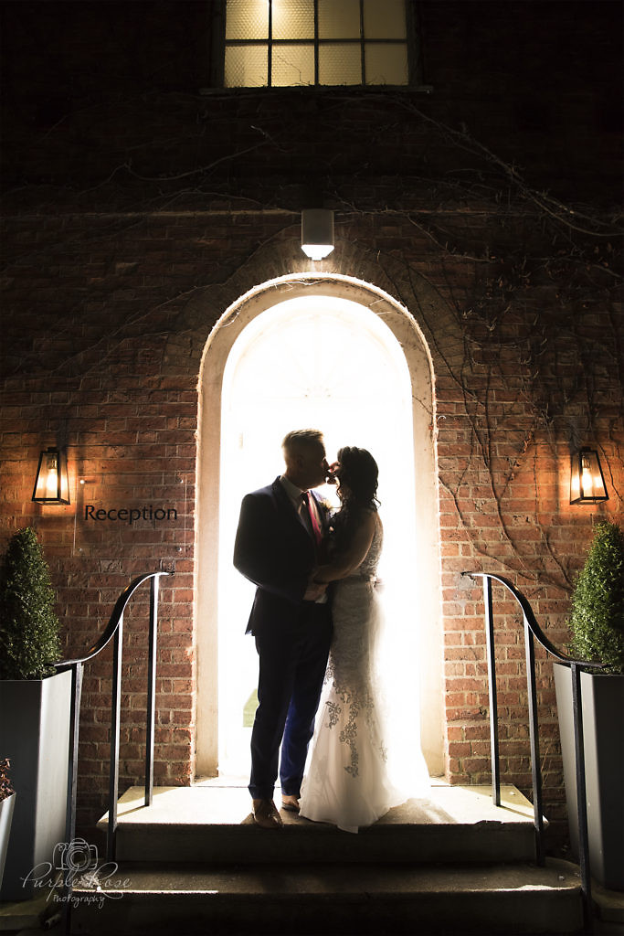 Night time photo of bride and groom stood in a doorway