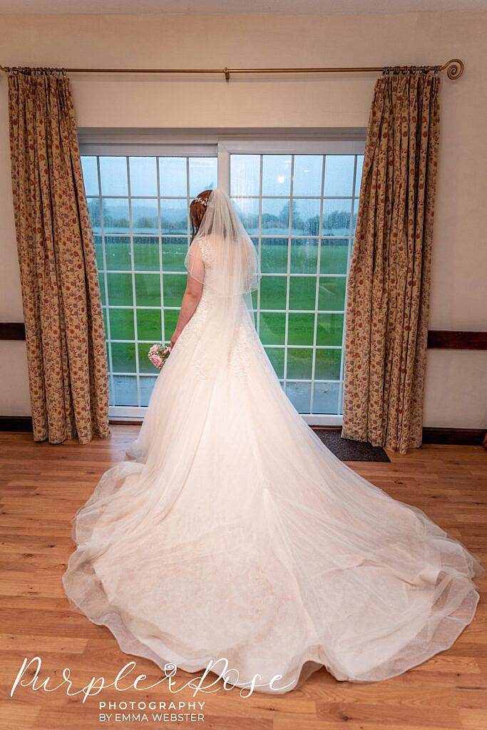 Bride standing at a window