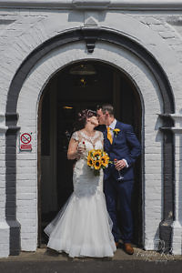 Bride and groom kissing in front of their wedding venue