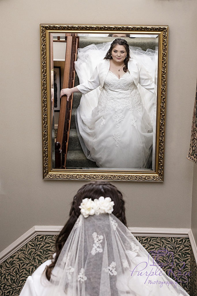 Bride viewing her reflection as she walks down some stairs