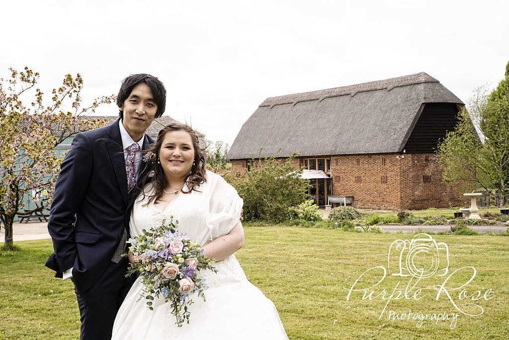 Bride and Groom standing in front of the Thatched Barn