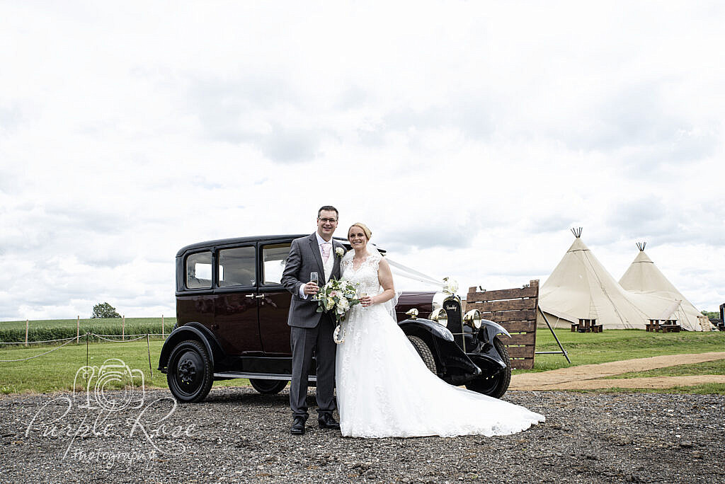 Bride and groom in front of their car and reception venue
