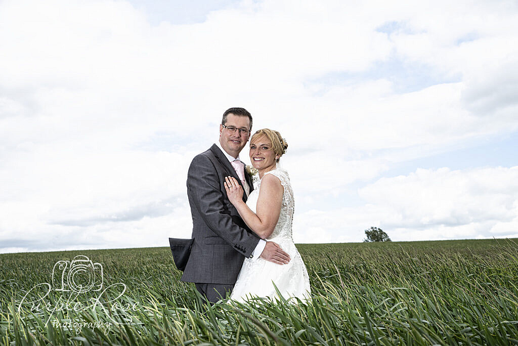 Bride and groom embracing on a windy day
