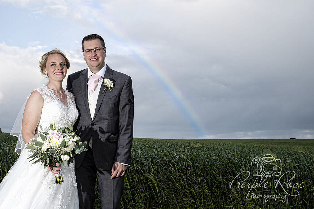 Bride and groom standing in front of a rainbow