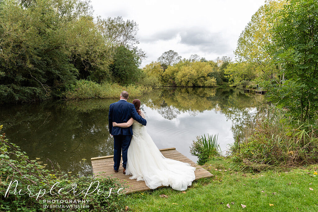 Bride and groom looking out onto a lake