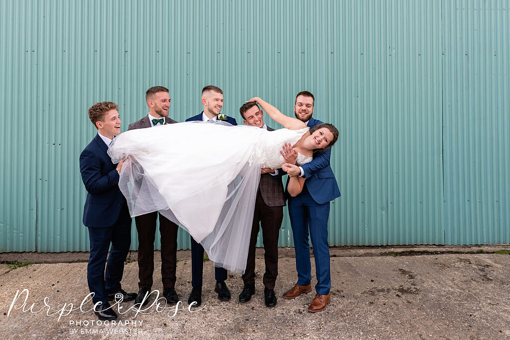 Groomsmen carrying the bride
