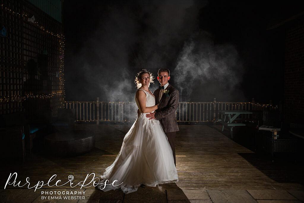 bride and groom with a dark smokey back ground
