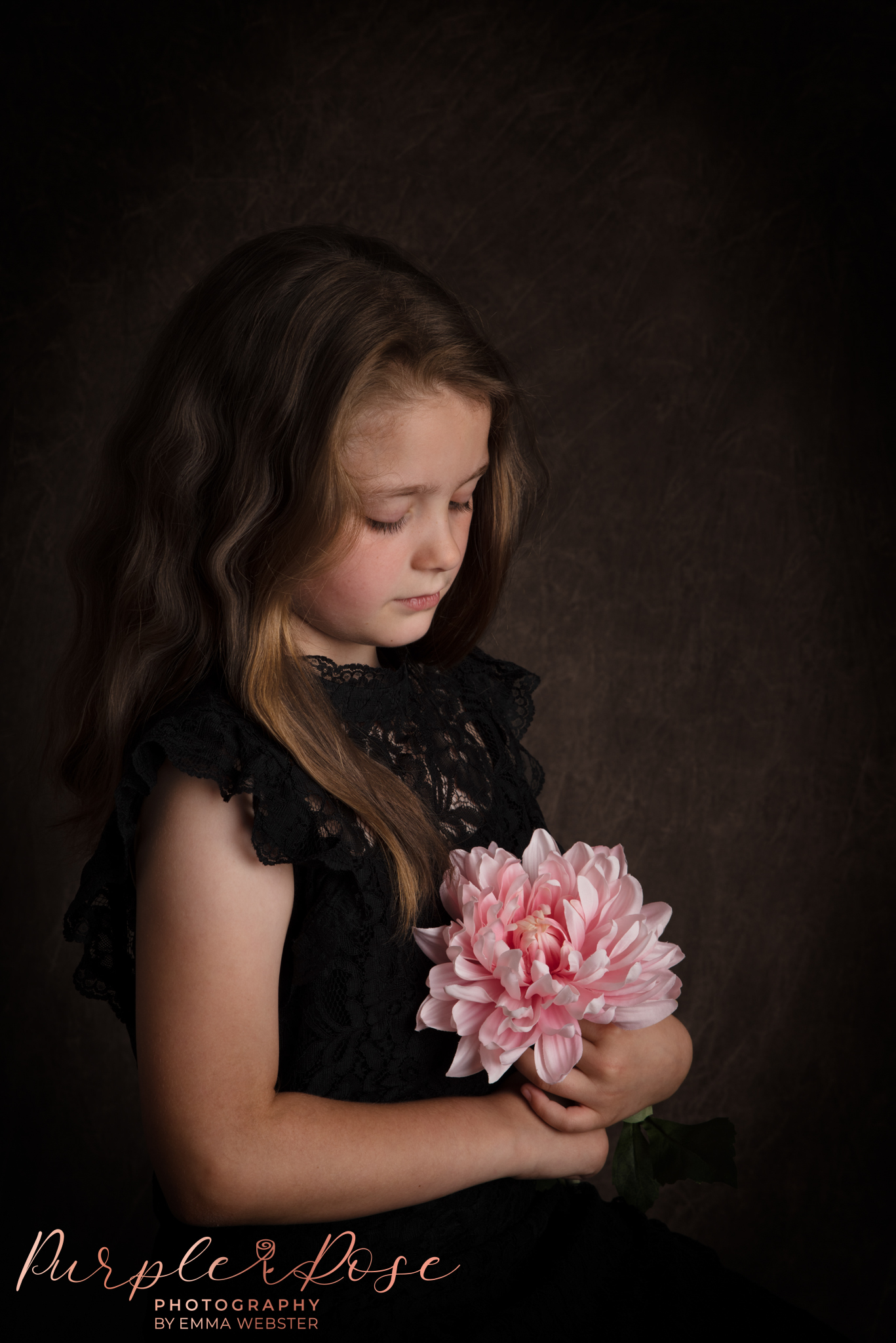 Child looking at a flower