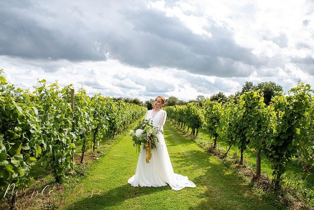 Bride holding bouquet in a vineyard