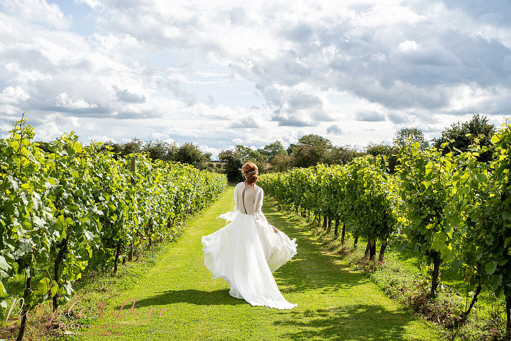 Bride skipping down a vineyard
