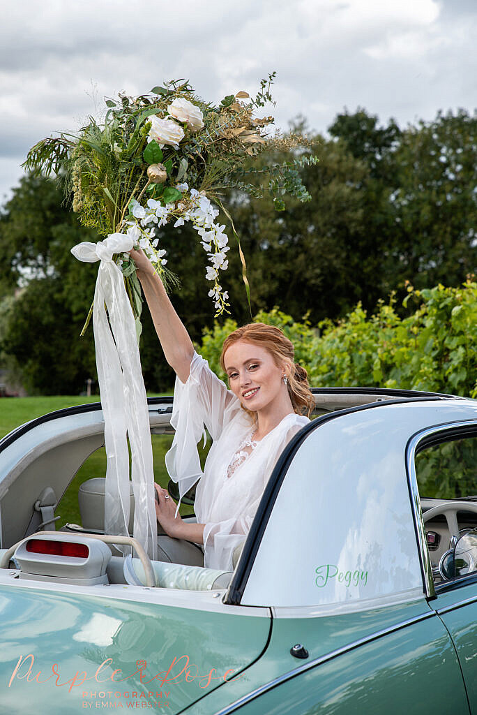 Bride standing out of car sun roof