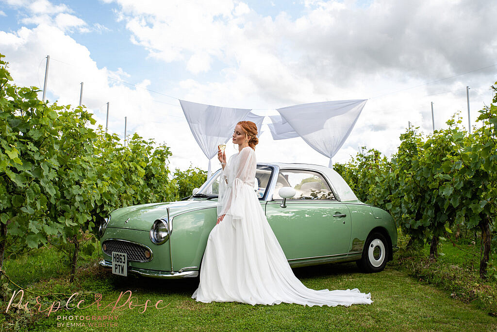 Bride stood in front of wedding car