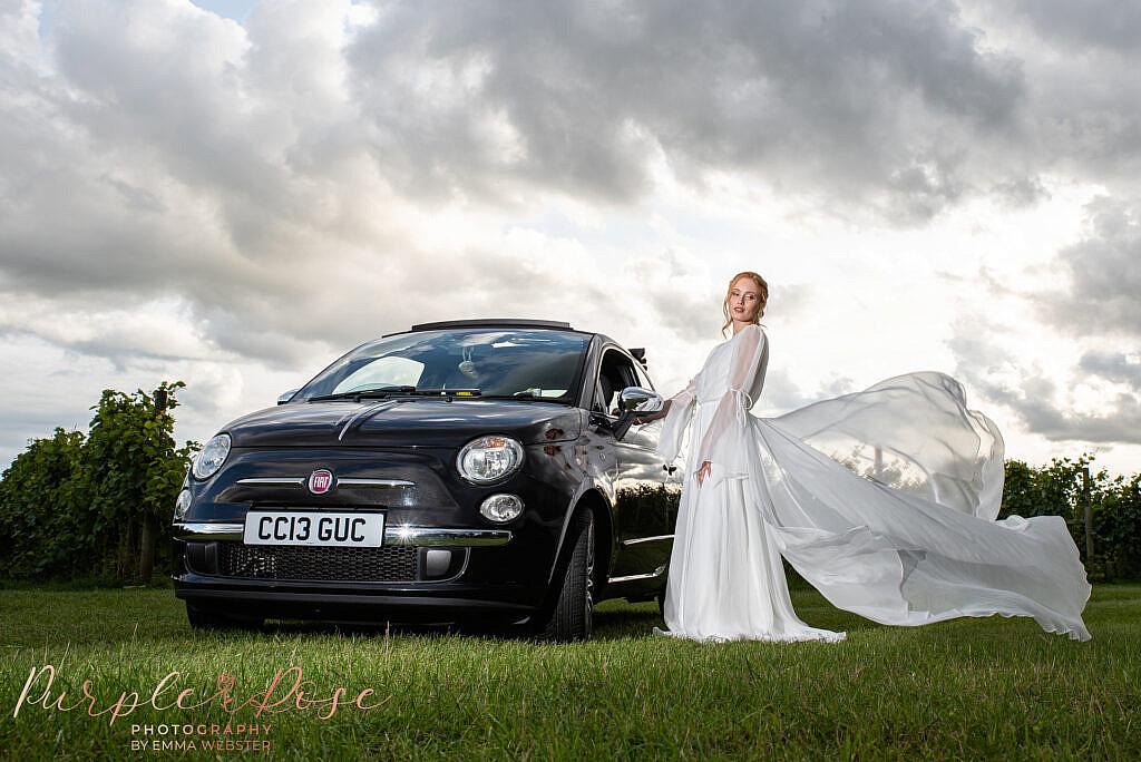 Bride stood next to wedding car