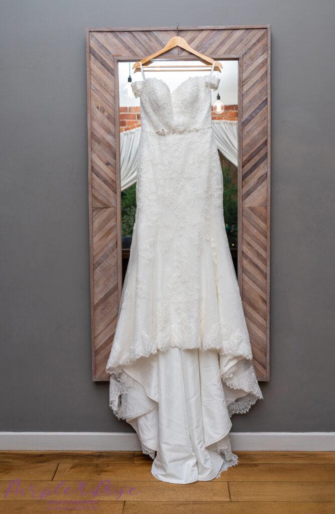 Wedding dress hanging on a mirror frame