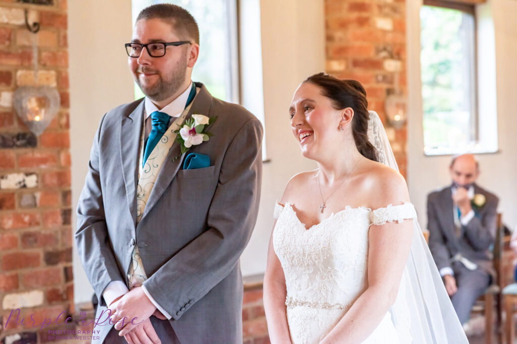 Bride and groom smiling during their wedding ceremony