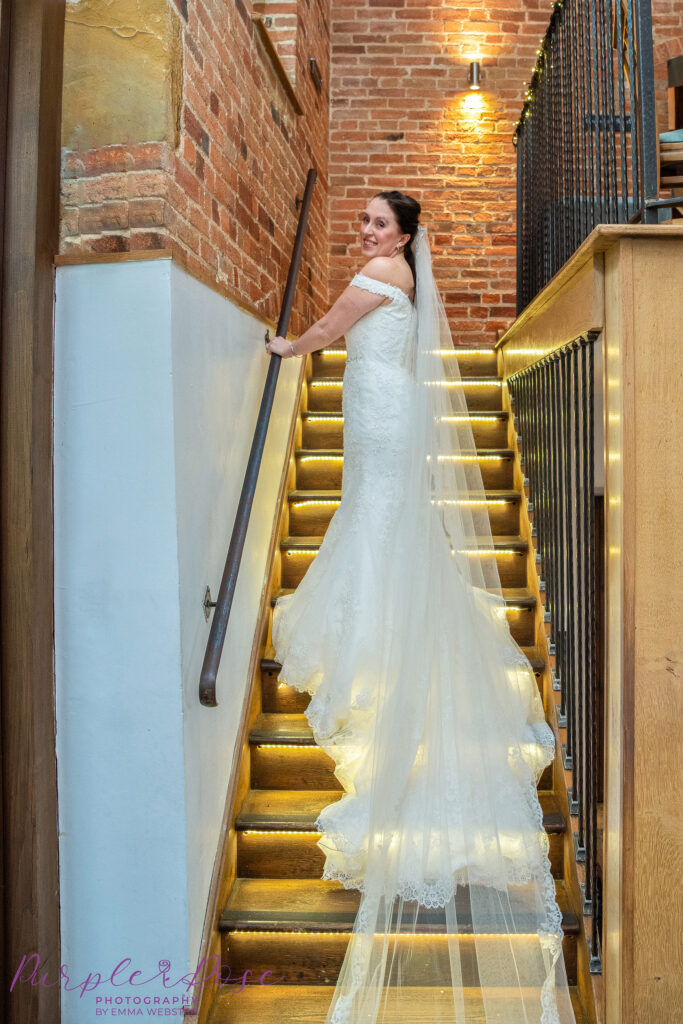 Bride walking up a backlit staircase