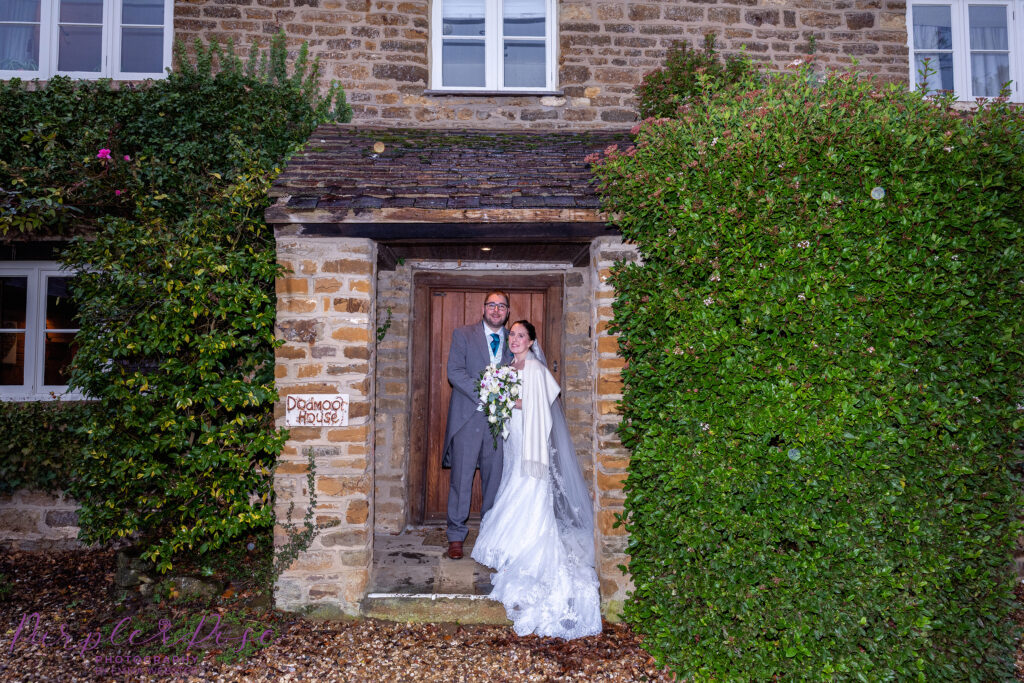 Bride and groom sheltering in a cottage door