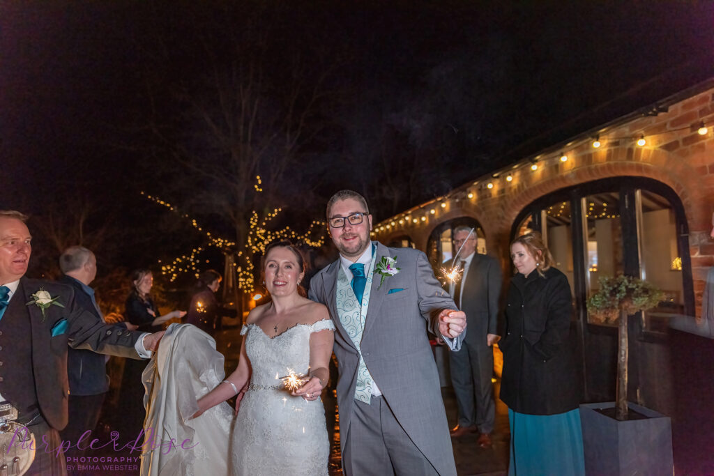 Bride, groom and guests playing with sparklers