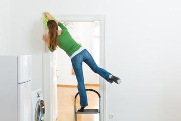 Women Leaning On Stairs Dusting Doorway