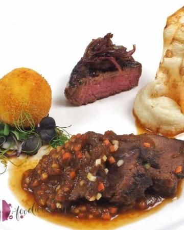 angerichteter Teller mit Rinderbacke, Filet und Kartoffelkugel