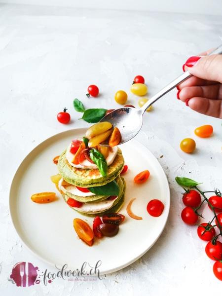 Die Pancakes werden mit Tomatensalat und Mozzarella serviert. Im Teig ist noch Basilikum, der die Pancakes herrlich grün färbt.