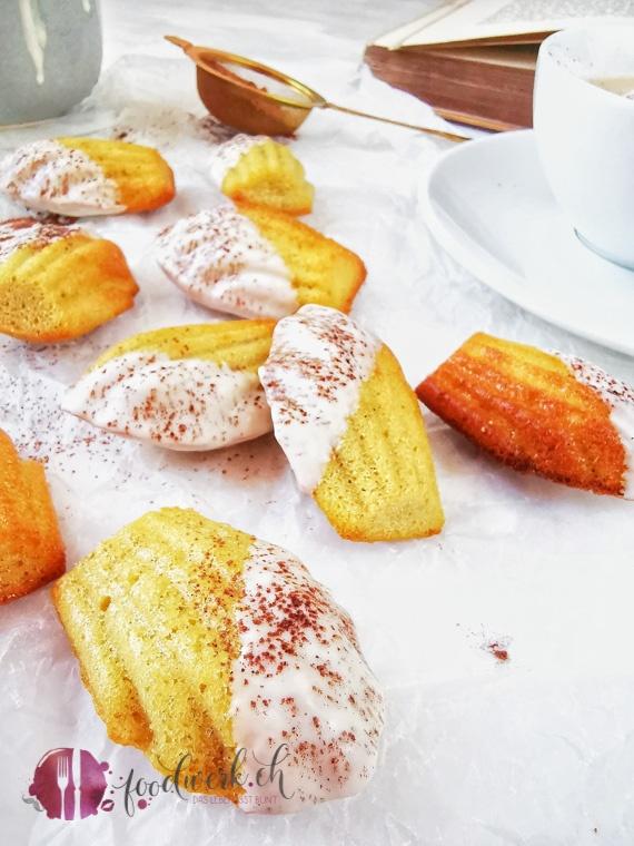 Cappuccino Madeleines auf Backpapier mit Kakaopulver und Kaffee