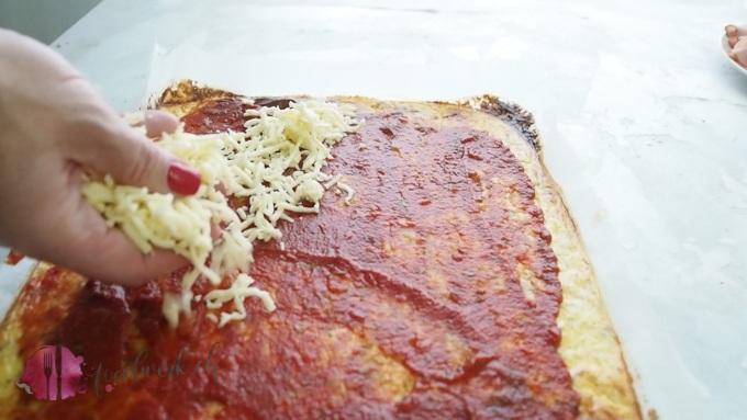Mit Tomatensauce und Käse belegen