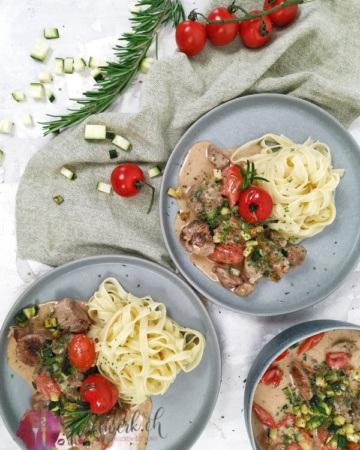 Truthan mit Gartengemüse und Nudeln auf Teller angerichtet