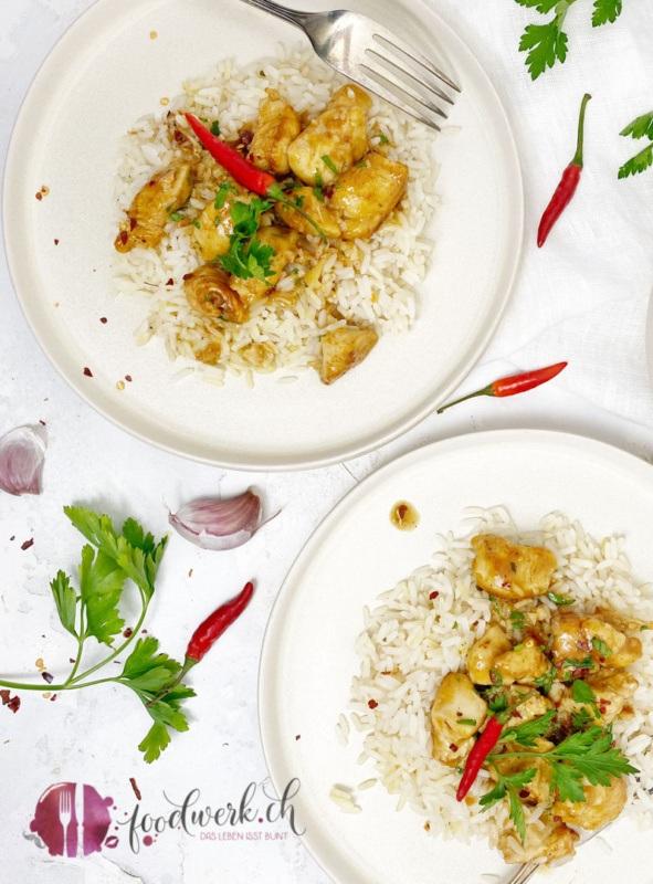 Zwei angerichtete Teller mit Reis und Knoblauch Honig Hähnchen mit Chili und frischer Petersilie