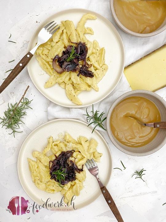 Quarkpizokel auf zwei Tellern mit Zwiebelschweize und Apfelmus sowie Schweizer Bergkäse