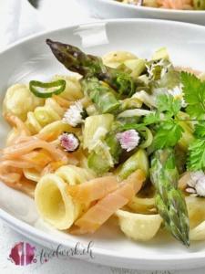 Ein Teller mit Pasta, grünem Spargelragout und Rauchlachs