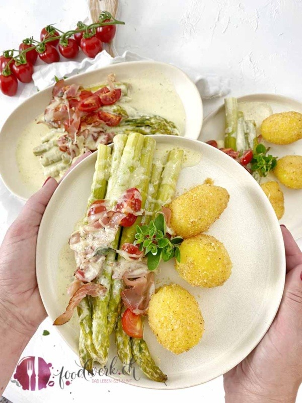 Angerichteter Teller mit grünen Spargeln und Sandkartoffeln