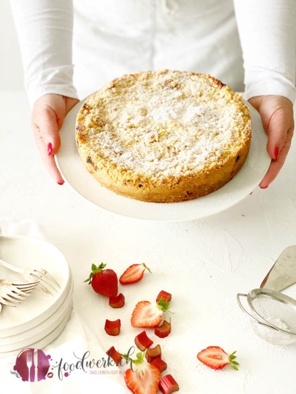 Der Streuselkuchen mit Erdbeeren und Rhabarber wird auf weisser Tortenplatte serviert