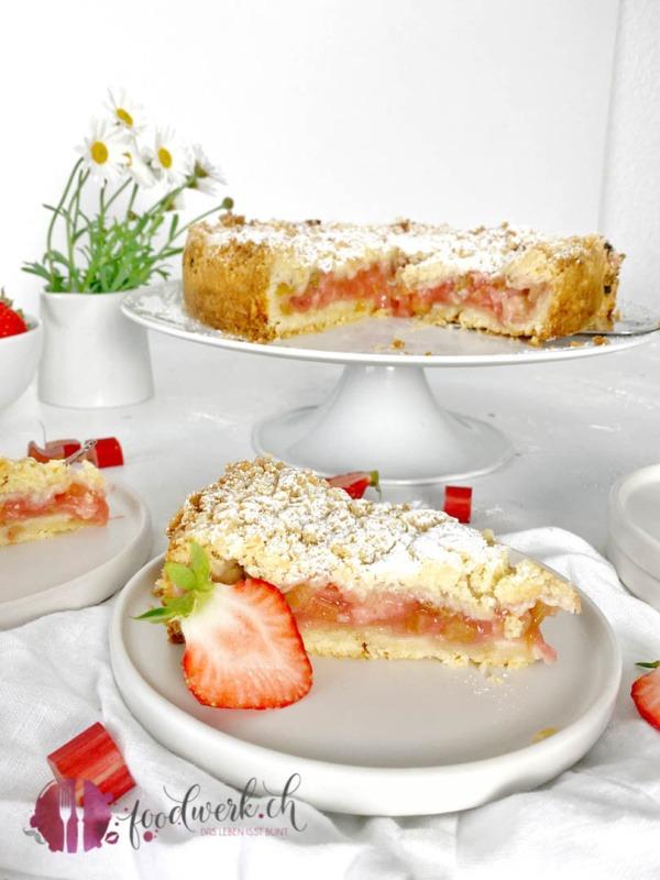 Streuselkuchen mit Erdbeeren und Rhabarber angeschnitten auf Teller und Tortenplatte