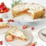 streuselkuchen mit erdbeeren und rhabarber auf weiser kuchenplatte serviert