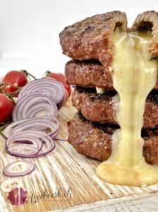 MIt Raclette Suisse gefüllte Rinds Burger, aufgeschnitten auf einem hellen Holzbrett und der Käse läuft aus den Burgern