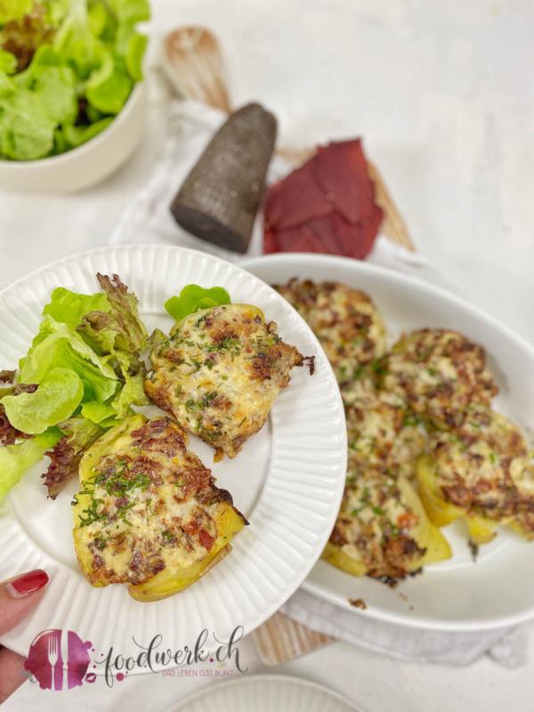 Appenzeller Quetschkartoffen mit Mostbröckli auf Teller mit Hand
