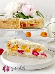 Streuselkuchen mit Aprikosen und Himbeeren auf weiser Tortenplatte mit Tortenschaufel