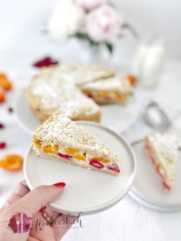 Himbeeren und Aprikosen Streuselkuchen auf weissem Teller serviert mit Hand im Bild