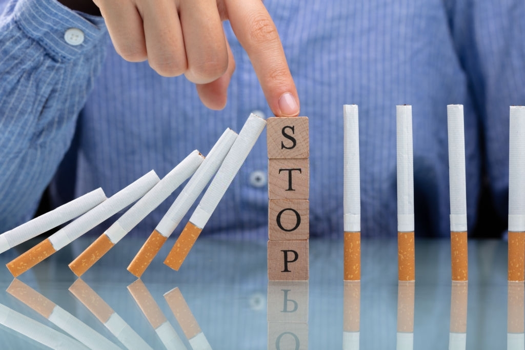 Woman Stopping Cigarette From Falling On Desk With Wooden Blocks