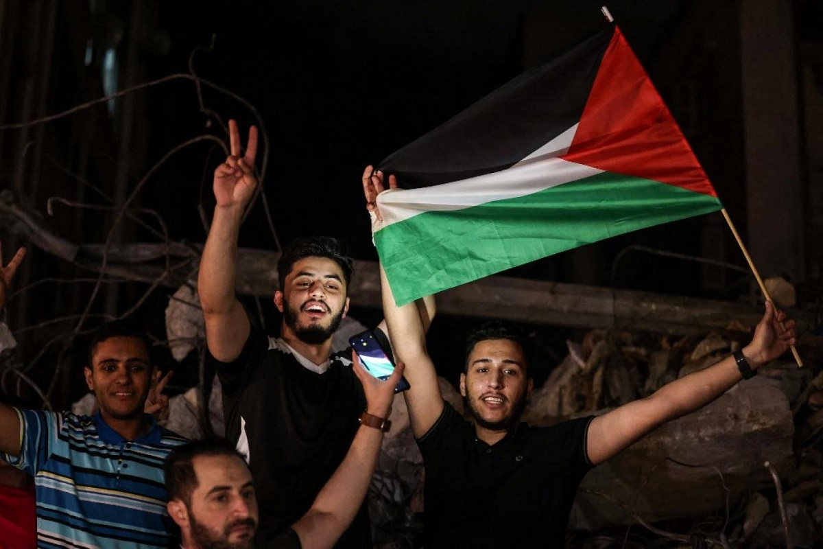 People wave the Palestinian flag as they celebrate in the street following a ceasefire brokered by Egypt between Israel and the two main Palestinian armed groups in Gaza on 21 May, 2021
