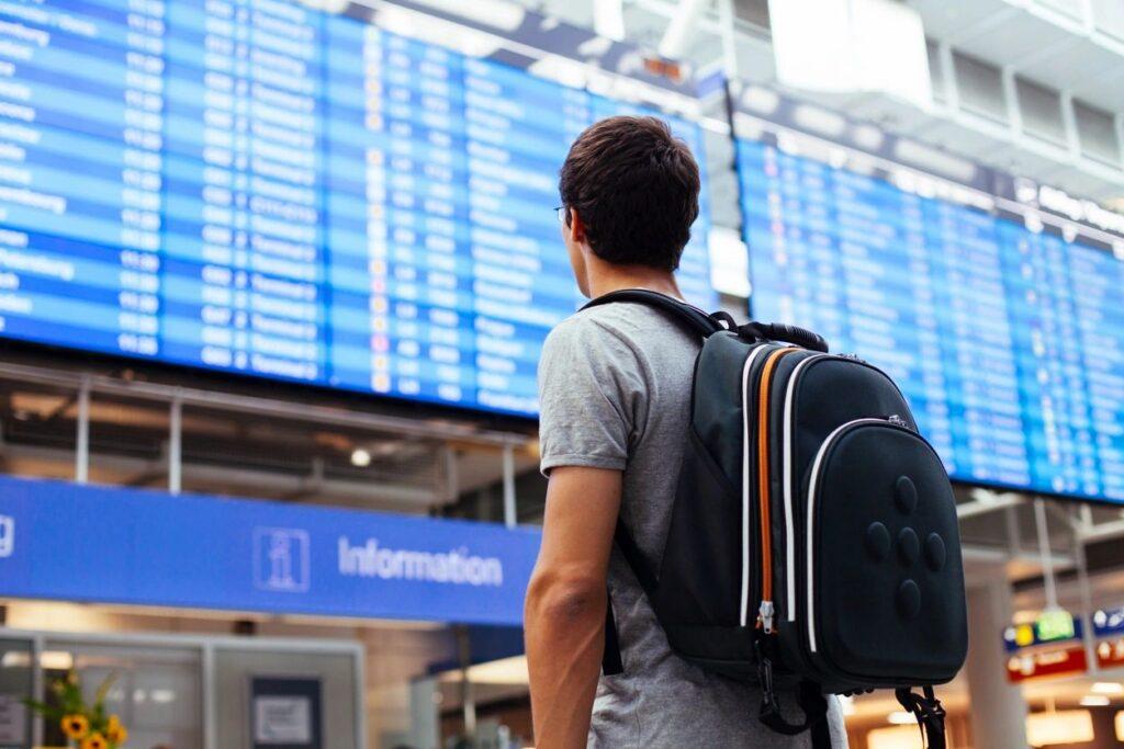 chico mirando pantallas del aeropuerto y microestancias