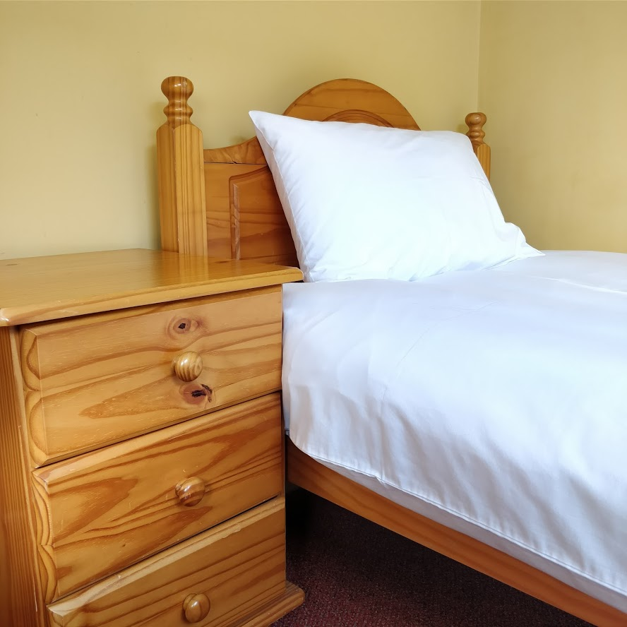 a single bed and a bedside drawer