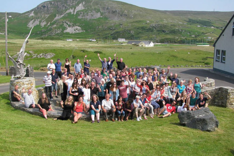 A group of people outside Oideas Gael Language School, enjoying the beautiful view of Donegal